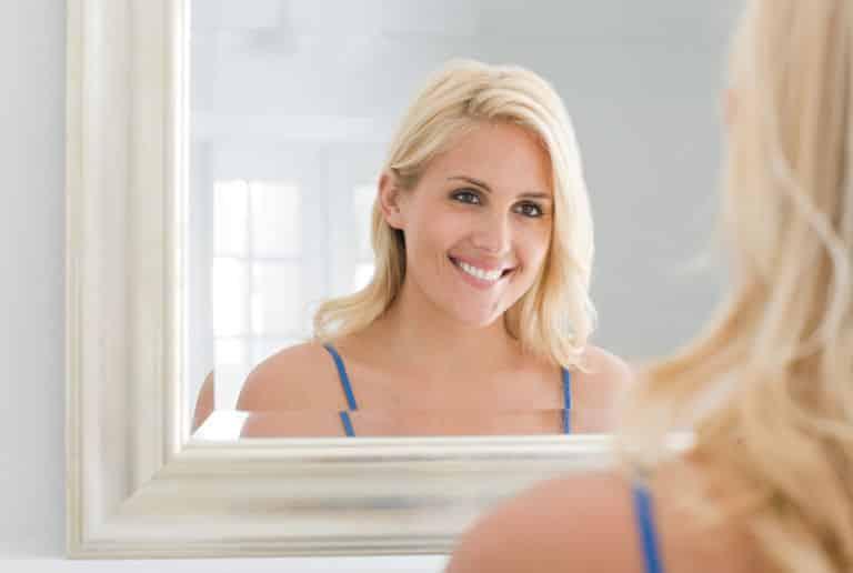 Femme se regarde dans le miroir en souriant
