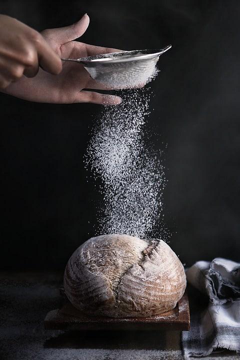 Farine saupoudrée sur une boule de pain frais par le boulanger
